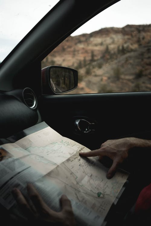 Crop faceless male traveler sitting in car and looking route in map during journey
