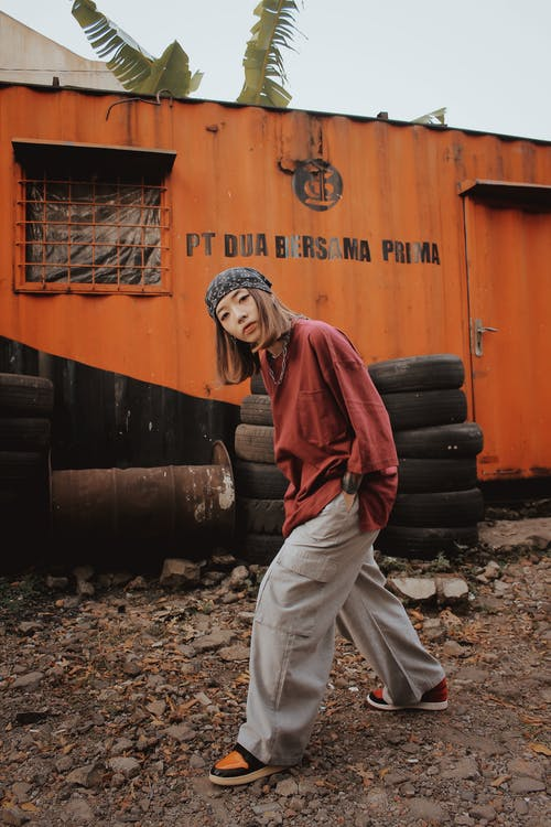 Serious young Asian woman with hands in pockets standing near old metal wagon