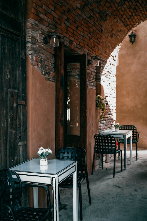 Tables and chairs placed on street near entrance to cafe in old brick building in daytime