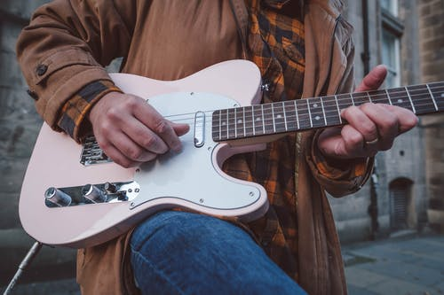 Person in Brown Leather Jacket Playing White Stratocaster Electric Guitar