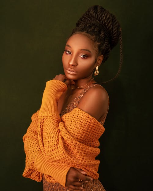 Attractive black female with light makeup and stylish hairdo in yellow sweater looking at camera while standing in studio