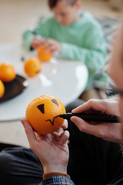 Man Making A Drawing On An Orange Fruit