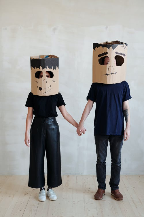 A Couple Wearing Diy Cardboard Box Mask While Holding Each Other's Hands