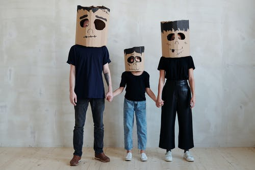 A Family Wearing Diy Cardboard Box Mask While Holding Each Other's Hands