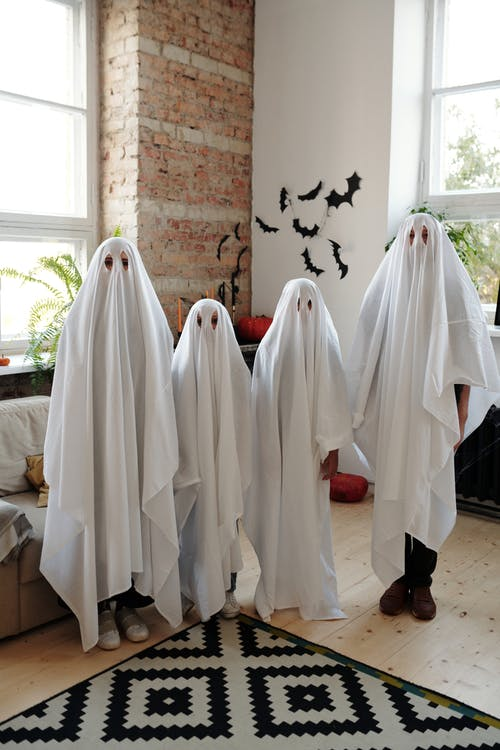 A Family Wearing White Halloween Costume While Standing in Living Room