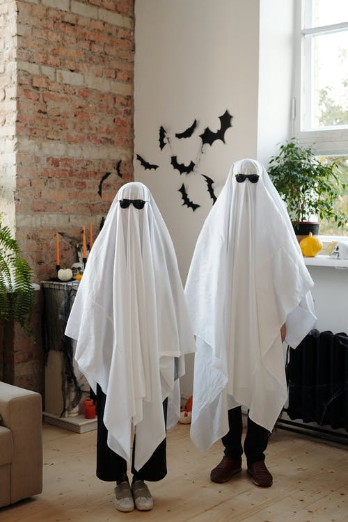 Two Persons Wearing a White Halloween Costume and Sunglasses