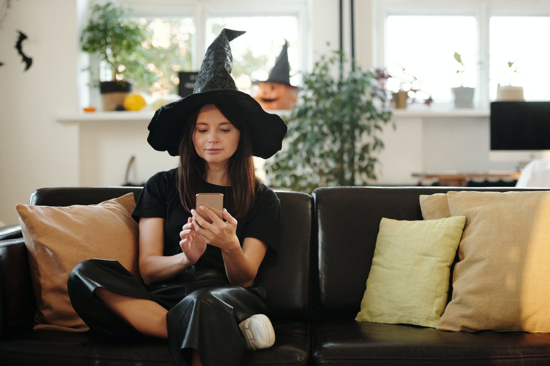 Woman in Black Shirt and Black Pants Sitting on Black Leather Couch While Using Her Cellphone