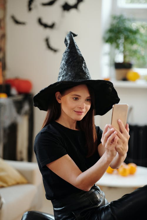 Woman in Black Shirt and Black Witch Hat While Taking a Selfie