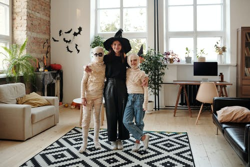 A Family Wearing Halloween Costumes While Smiling
