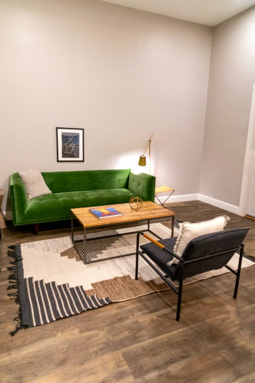 Living room interior design with small framed photo above cozy green sofa and wooden table on soft carpet