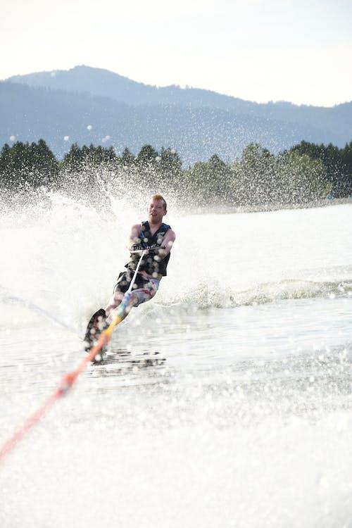 Excited sportsman practicing water skiing on splashing ocean