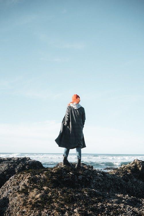 Faceless woman on rocky coast near sea