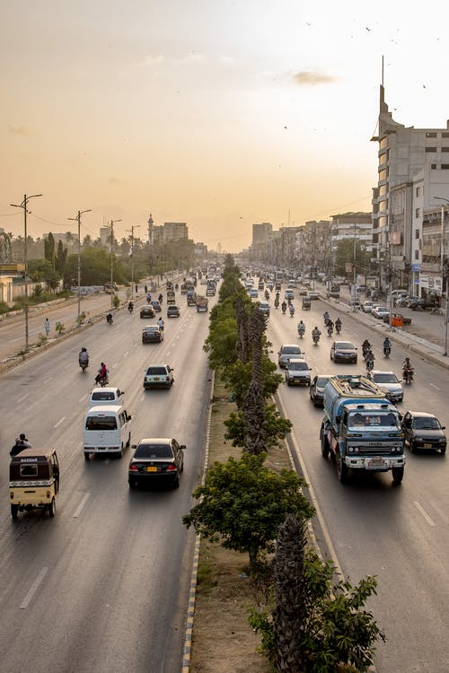 Heavy traffic in megapolis with residential houses and vehicles