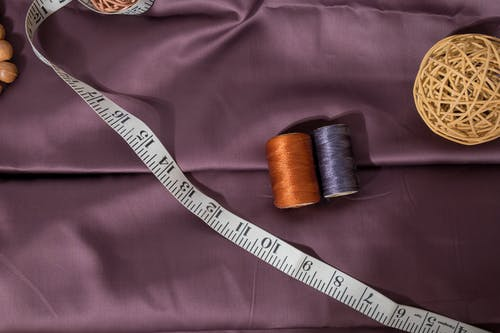 Top view composition of sewing reels of yarn placed between white measuring tape and wicker ball placed on violet fabric