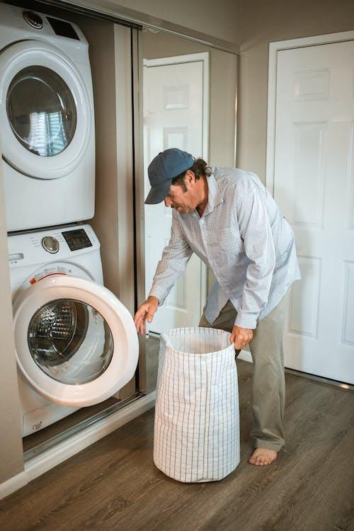 Man in White Dress Shirt Standing Beside White Front Load Washing Machine