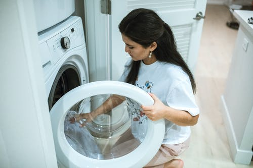 Woman in White Shirt Standing in Front of White Front Load Washing Machine