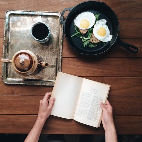 Crop person at table with book and breakfast