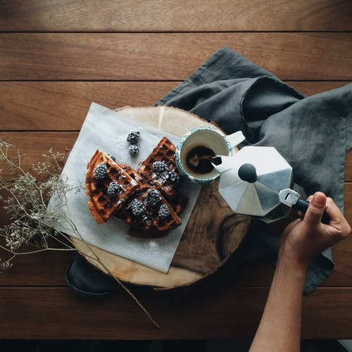 From above of crop anonymous person holding pot and pouring coffee in mug near fresh waffles with berries