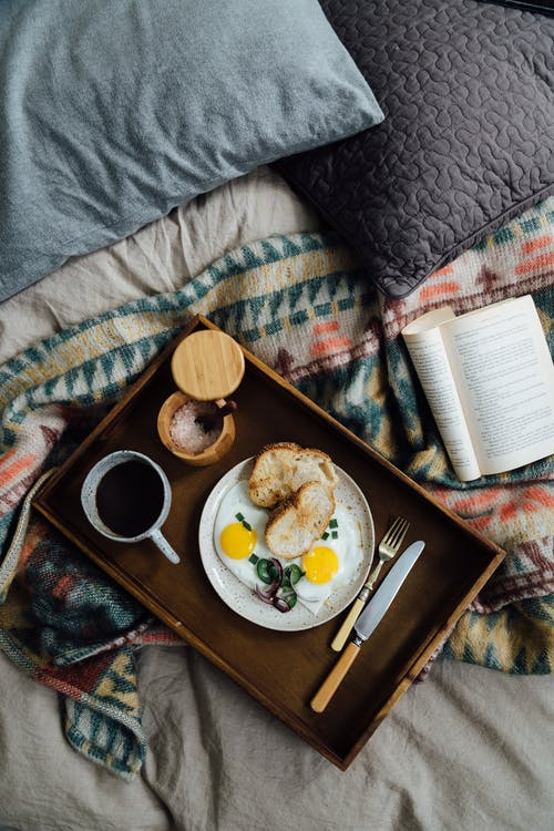 Tray with breakfast on bed near book