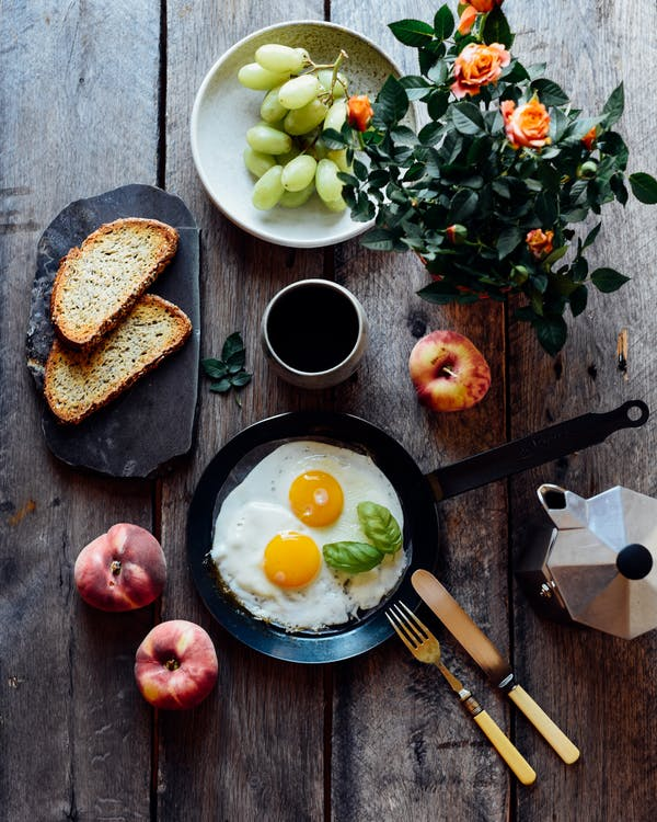 Top view of fried eggs with mint in pan near fruits and bread on wooden table
