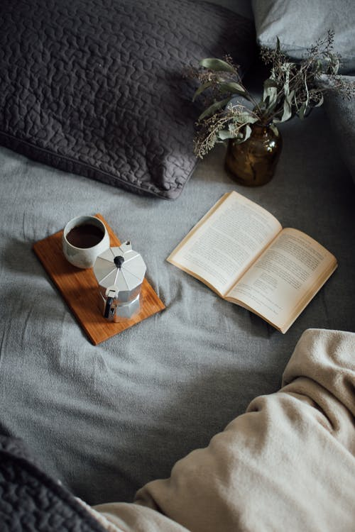 Coffee with book on cozy bed