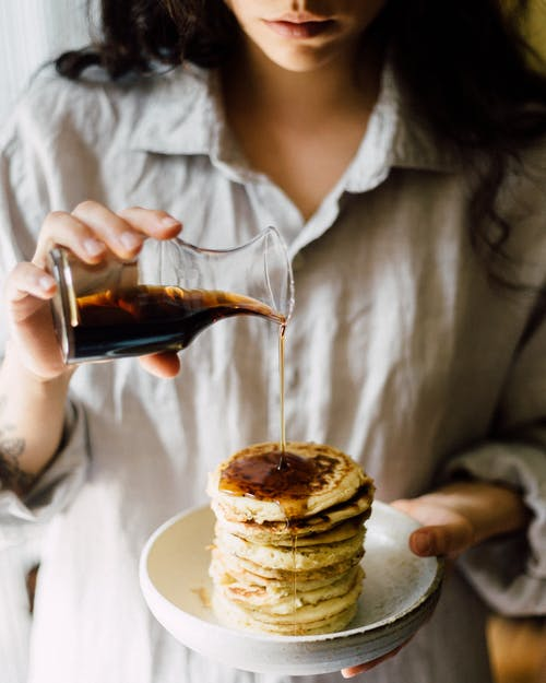 Crop woman pouring syrup on pancakes