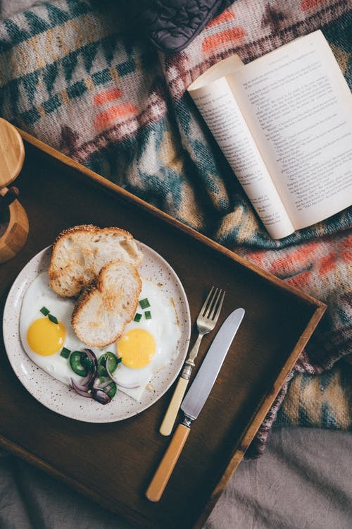 From above of opened book on bed near wooden tray with delicious breakfast from fried eggs and onion