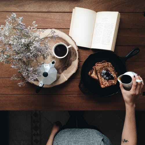 Crop woman with dessert and book