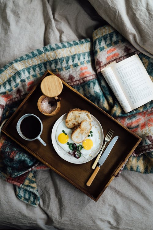 From above of fresh breakfast from fried eggs with bread near coffee and opened book on blanket