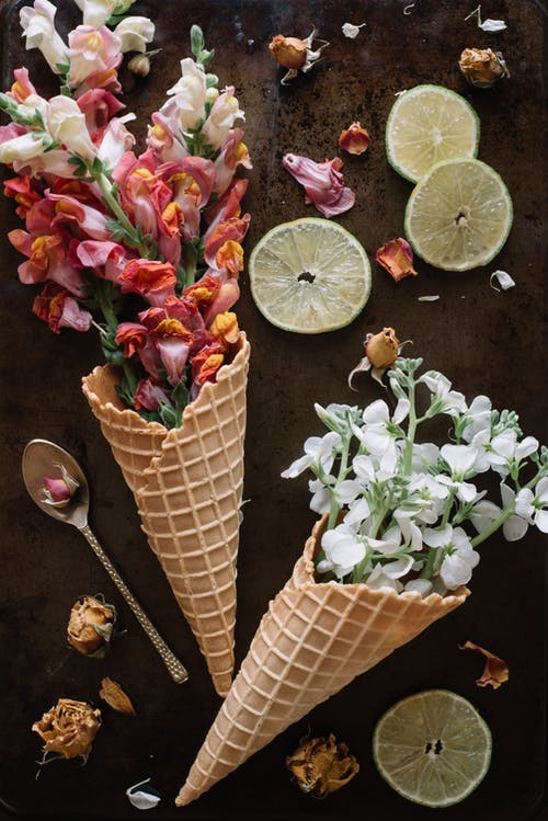 Fresh flowers in waffle cones near lemon