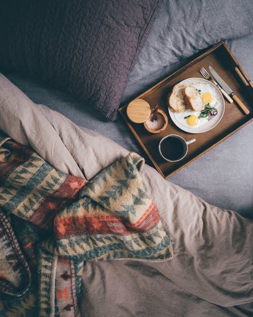 Tray with fresh breakfast on bed