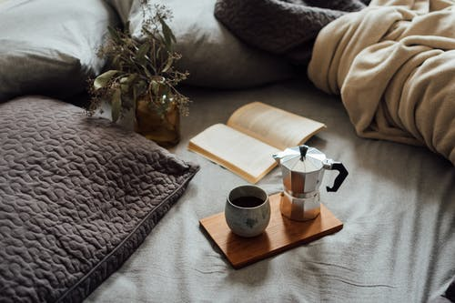 From above of cup of hot coffee with pot on wooden tray near open book and dry plant in cozy bed