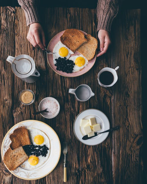 From above of crop anonymous person in sweater holding fork and plate with delicious breakfast on table with cup of coffee and butter