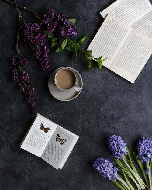 Opened books and coffee near flowers