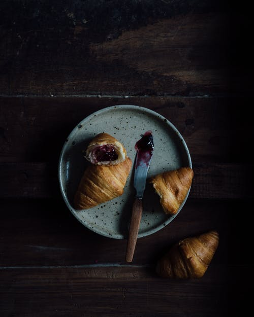From above of fresh baked croissants with jam in ceramic plate near knife on wooden table