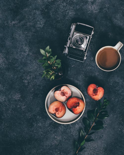 Cup of coffee near fruit and camera