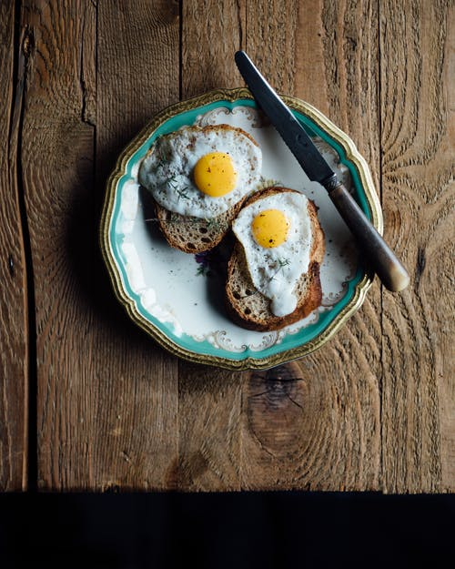 From above of appetizing fried eggs on toasts in plate near knife on wooden table