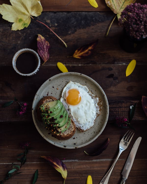 Top view of avocado toast with fried eggs and mug of fresh coffee with bright autumn leaves on wooden table