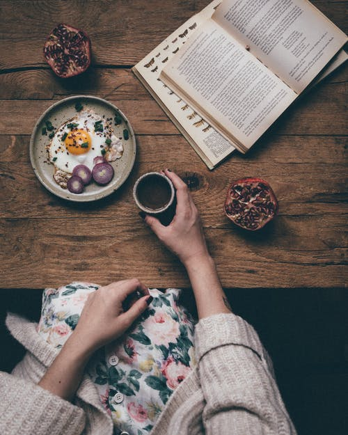 From above of crop unrecognizable female holding cup of hot coffee at table with fresh breakfast and pomegranate while reading
