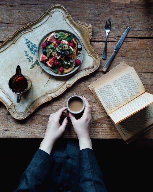 Crop woman with book and breakfast