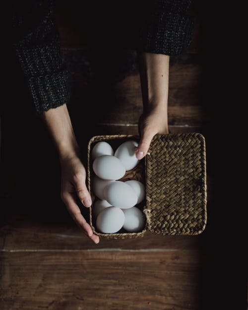 Person Holding White Eggs on Brown Wooden Tray