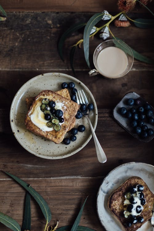 From above of delicious toasts with berries on plate and cup of coffee near fresh green plants on wooden table