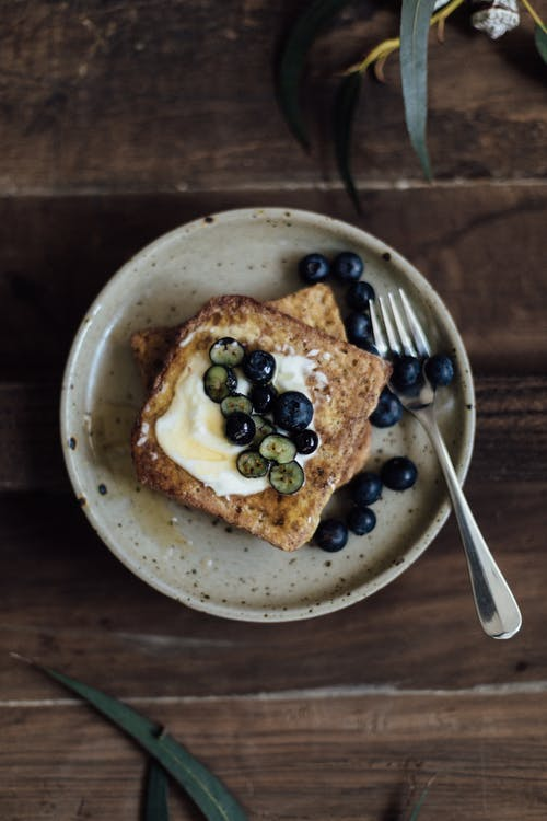 Top view of appetizing fresh bread with fresh blueberries and sauce served on plate on wooden table with fork in kitchen with plant