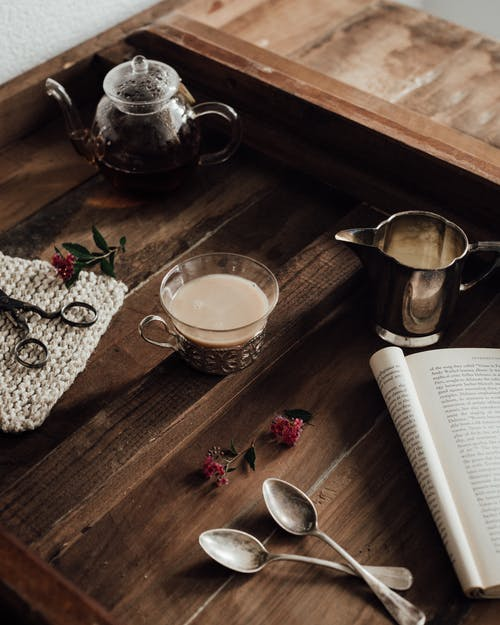 From above of hot coffee with mil near saucer served on wooden tray with glass teapot and opened book in morning