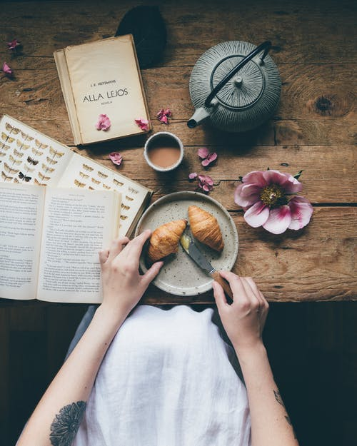 Crop woman with croissants near table