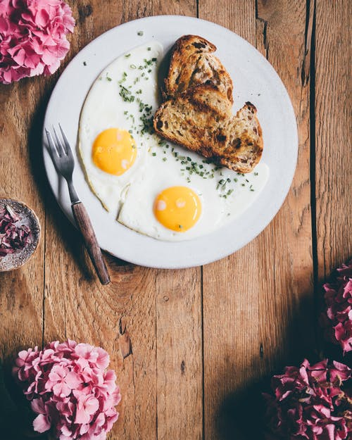 From above of appetizing fried eggs served on white plate with bread placed on wooden table with pink flowers in morning