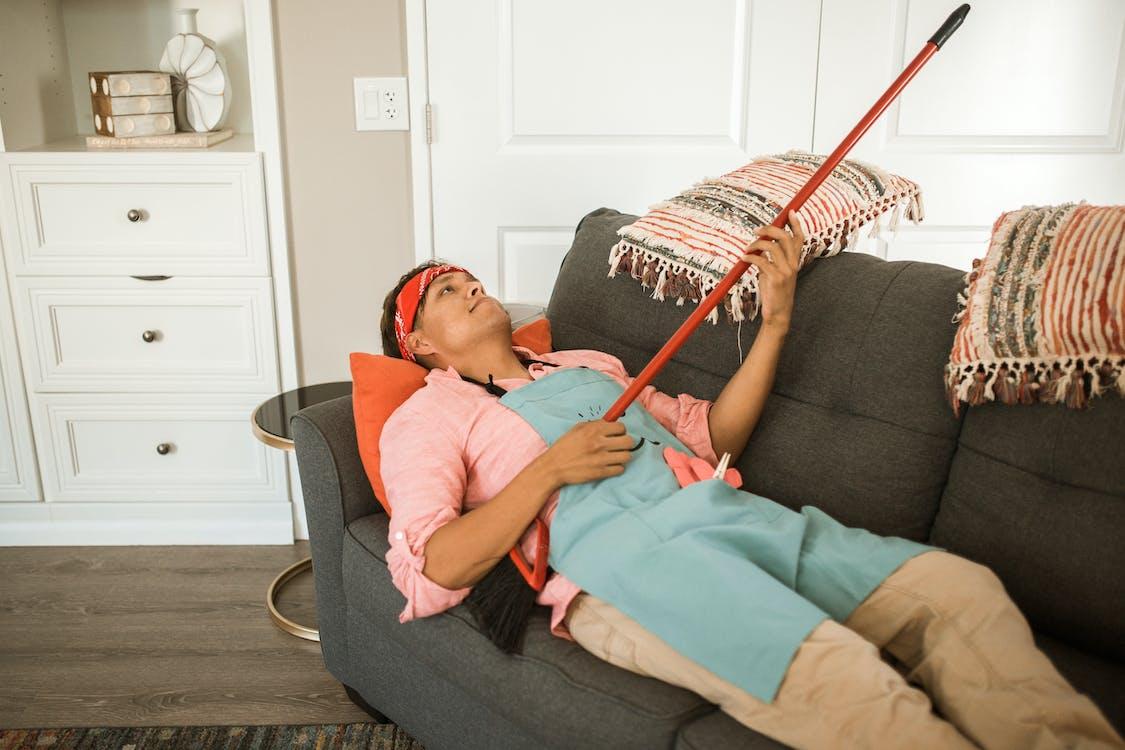Woman in Pink Shirt Lying on Black Sofa