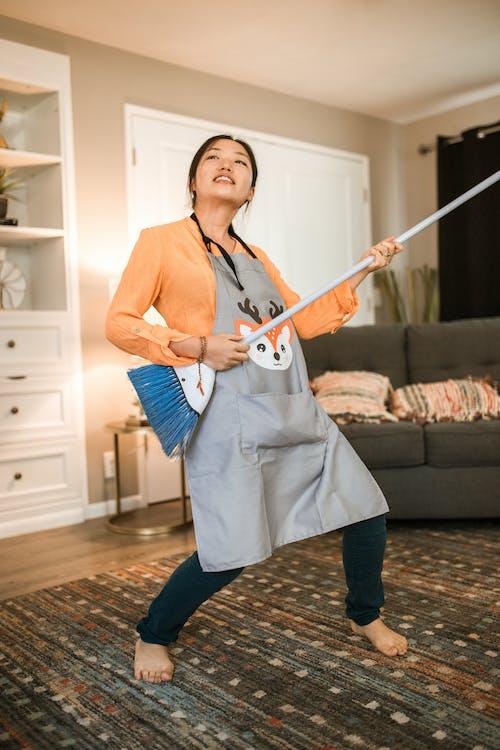 青と白のエレキギターを保持している白いノースリーブのドレスの女性