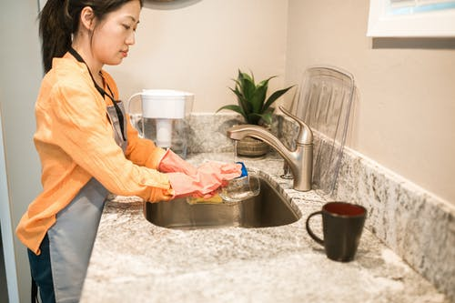 オレンジ色のドレスシャツと透明なガラスのボウルを保持している灰色のズボンの女性