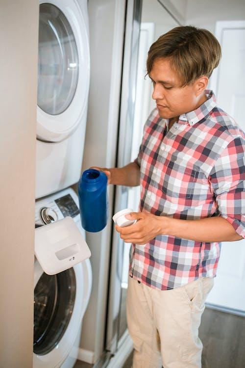 青いプラスチックボトルを保持している赤白と青の格子縞のボタンアップシャツの男
